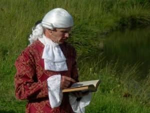 Carl von Linné läser i sin bok.